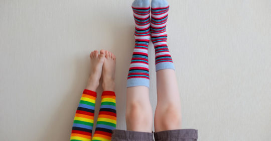 Funny picture of inverted children's feet in very bright striped socks on a light wall. Close up. Childhood concept (Funny picture of inverted children's feet in very bright striped socks on a light wall. Close up. Childhood concept, ASCII, 116 compon